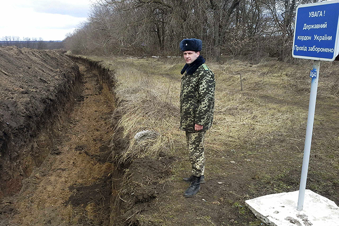 An Ukrainian army officer stands by a ditch at the Ukrainian-Russian front near the border crossing of Novoazovsk
