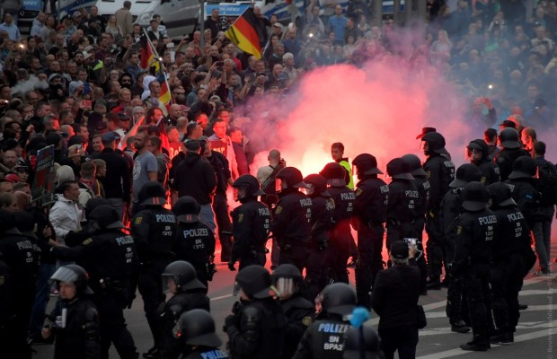 Riot policemen stand guard as the right-wing supporters protest after a German man was stabbed last weekend in Chemnitz